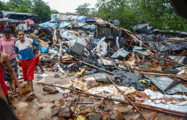 Debris seen after a portion of a compound wall collapsed on shanties adjacent to it due to heavy rainfall. (PTI Photo)