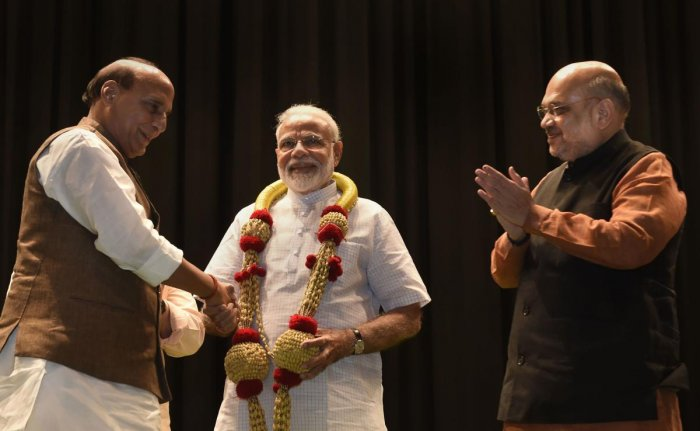 Prime Minister Narendra Modi is garlanded by Bharatiya Janata Party (BJP) senior leaders Amit Shah and Rajnath Singh during the BJP parliamentary party meeting, in New Delhi, Tuesday, July 02, 2019. (PTI Photo)