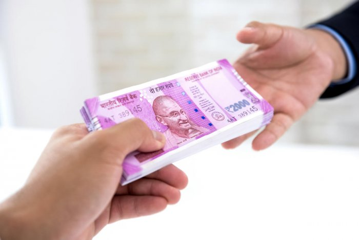 Businessman handing over a wad of crisp new Indian rupee banknote money to his partner against white blur background. (Getty Images)