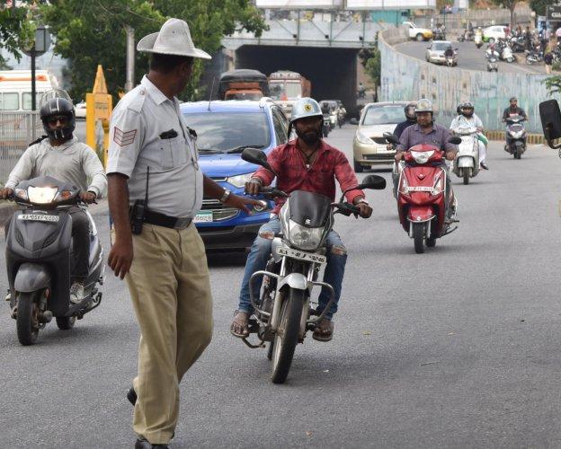 Traffic police stop vehicles for traffic rules violation on Outer Ring road near Nagarabhavi in Bengaluru. DH Photo/Janardhan B K