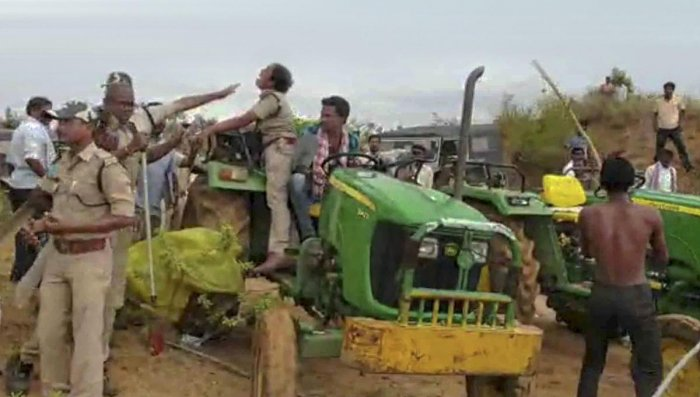 Chole Anitha, a female forest officer, climbs on a tractor to save herself from the brutal attack of the farmers, who were protesting against the ploughing of land by the forest department for a mass plantation programme, at Sarsala village in Kaghaznagar.