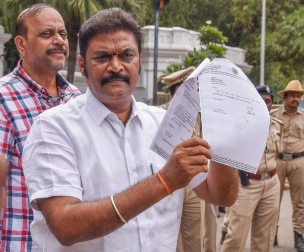 Anand Singh, MLA, Vijayanagar, Ballari district, shows a copy of his resignation letter after after submitting it to Governor at Raj Bhavan in Bengaluru on Monday. DH Photo/S K Dinesh