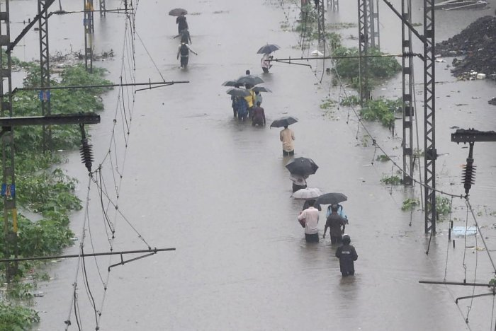 People walk on the waterlogged railway tracks during heavy monsoon rain at Tilak Nagar station in Mumbai on Tuesday. PTI photo