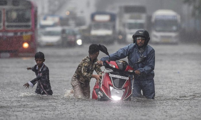 People wade through a waterlogged street after heavy rain lashed Mumbai on Tuesday. PTI