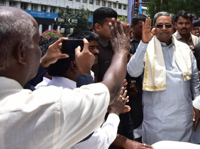 Former chief minister Siddaramaiah waves at his supporters during a programme organised by Karnataka Scheduled Castes and Scheduled Tribes Contractors' Association in Bengaluru on Tuesday. DH Photo