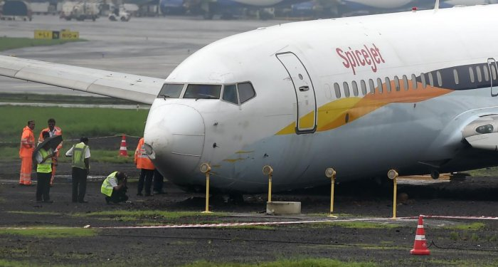 A SpiceJet aircraft is surrounded by airport staff as it stands stranded off the tarmac at Chhatrapati Shivaji Maharaj International Airport in Mumbai on July 2, 2019, after it overran the runway while landing during heavy rain, causing no injuries. AFP p