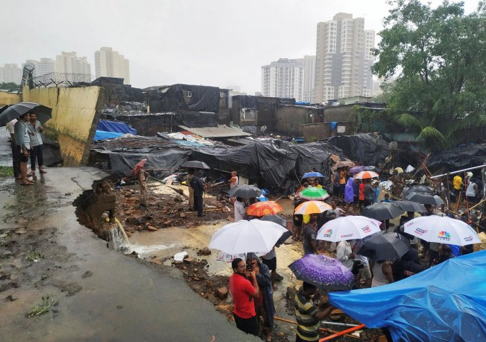 People stand among the debris after a wall collpased on hutments due to heavy rains in Mumbai, India July 2, 2019. REUTERS