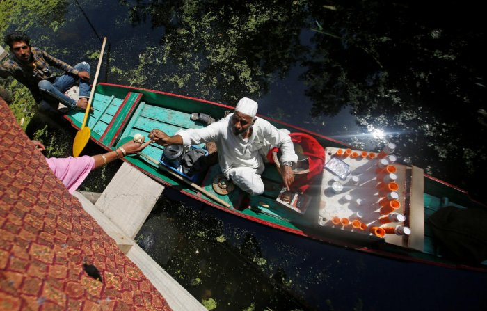 A vendor sitting on a boat sells ice cream at Dal Lake in Srinagar on June 27, 2019. REUTERS