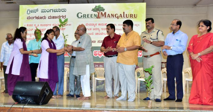 Dr Vaman Shenoy, president of the Green Mangaluru Programme, gives a sapling to a student during the launch of the programme in Mangaluru.