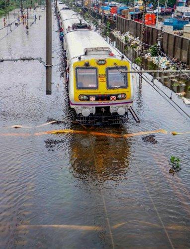 A suburban local train moves across submerged railway tracks following heavy monsoon rains, in Mumbai. (PTI Photo)