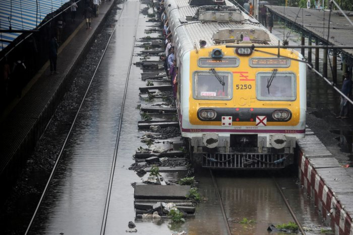 A passenger train moves through a water-logged track during heavy rains in Mumbai. (Photo by REUTERS)