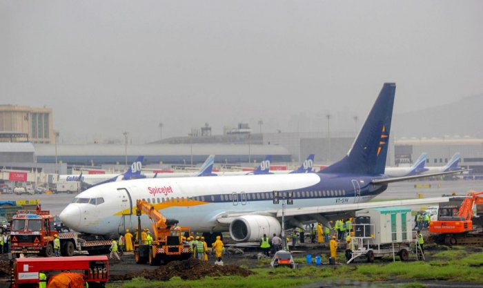 A team of engineers and technicians from Air India work to remove the SpiceJet aircraft from the runway at Chhatrapati Shivaji Maharaj International Airport, in Mumbai. (PTI Photo)