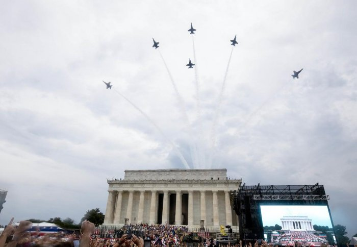 """As combat aircraft, including the rarely seen B2 stealth bomber flew overhead, Trump scrolled through myriad events of US history, from groundbreaking inventions to battlefield victories, drawing cheers of """"USA! USA!"""" from an enthusiastic rain-soaked audi"""