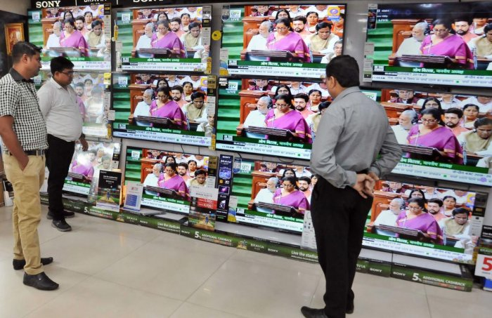 People watch Finance Minister Nirmala Sitharaman tabling the Union Budget 2019-20, on TV sets at a showroom in Kolkata, Friday, July 5, 2019. (PTI Photo)