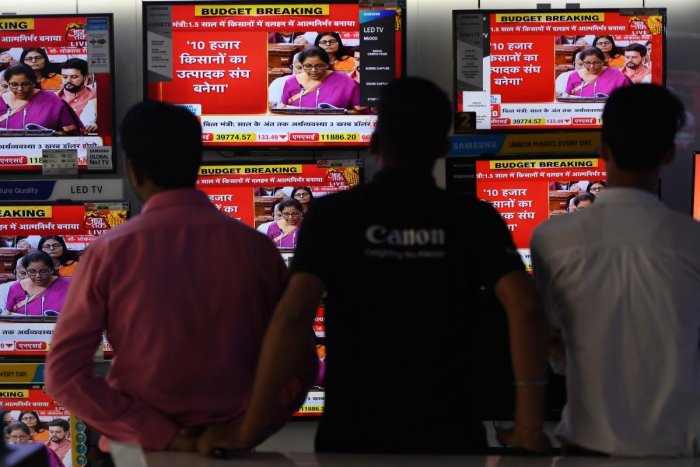 Salesmen watch Indian Finance Minister Nirmala Sitharaman delivering her budget speech on television screens at an electronics store in New Delhi on July 5, 2019. (AFP)