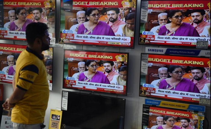 A salesman watches Indian Finance Minister Nirmala Sitharaman delivering her budget speech on television screens at an electronics store in New Delhi on July 5, 2019. (AFP)