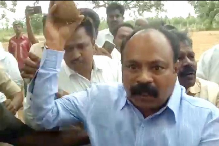 MLA K Annadani tries to hit a Congress worker with coconut during a groundbreaking ceremony in Malavalli taluk of Mandya district, on Friday.