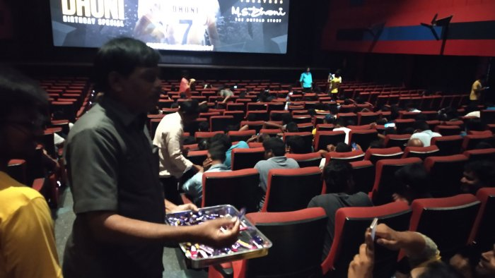 Fans distributing chocolates during the screening of MS Dhoni biopic. (Image courtesy Twitter)