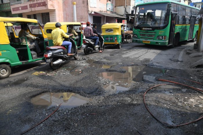 Motorists are struggle to drive on a Big Pothole on the Tannery road in Bengaluru on Tuesday. Photo/ B H Shivakumar
