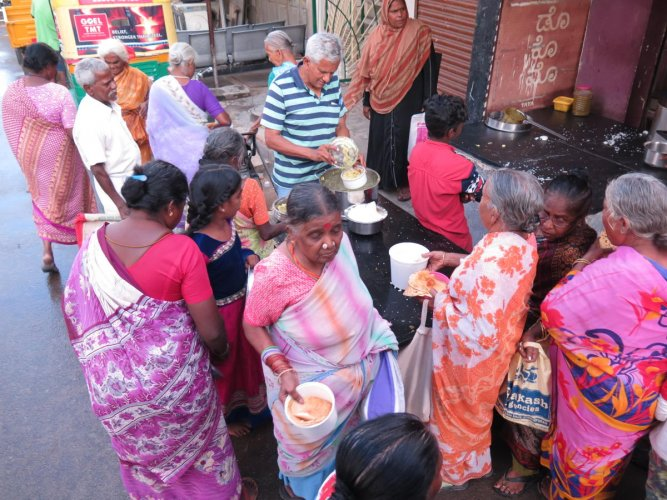 Needy residents of the Rajendranagar slum in Bengaluru collect fresh food distributed by an NGO. dh photo/ akhil kadidal