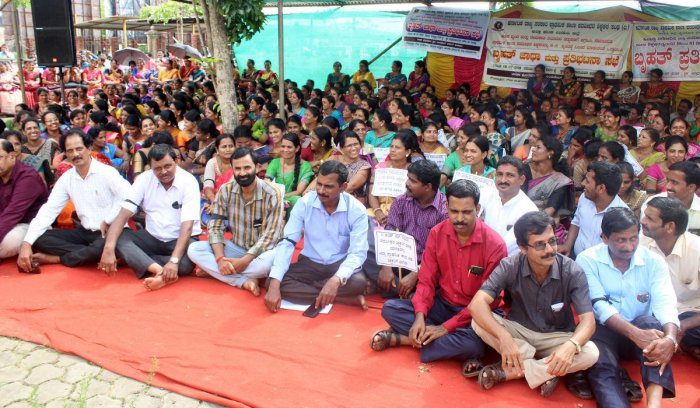 Teachers stage a protest in front of the deputy commissioner's office in Manipal on Saturday.