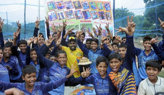 Fans celebrate the 38th birthday of cricketer Mahendra Singh Dhoni outside his residence at Harmu, Ranchi. (PTI Photo)