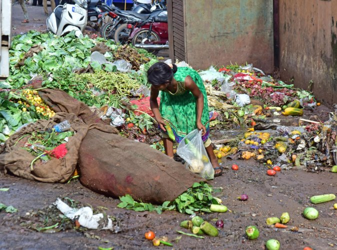 A girl forages for edible vegetables in the garbage near Central market in Mangaluru. (DH Photo/Govindaraj Javali)