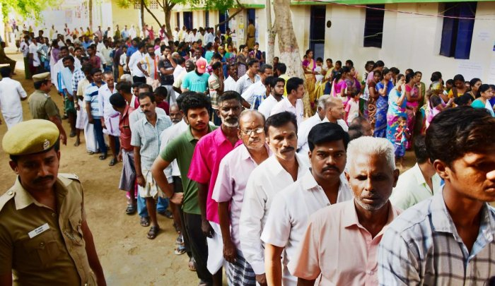 Voters wait in queues to cast their votes at a polling station, during the by-election for Thiruparankundram Assembly seat, in Madurai, Sunday. PTI Photo