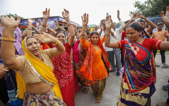 Pilgrims dance and chant religious slogans after the Amarnath Yatra was suspended due to the third death anniversary of former Hizbul Mujahideen commander Burhan Wani, at Bhagwati Nagar base camp in Jammu, Monday, July 8, 2019. PTI