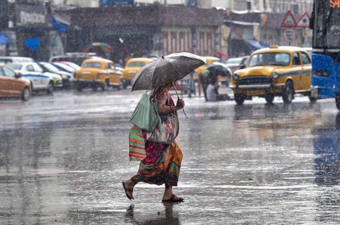 A pedestrian rushes to cross a busy city street during pre-monsoon rainfall, in Kolkata. PTI file photo