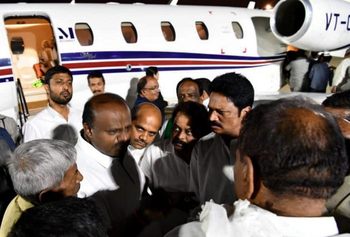 Karnataka CM H D Kumaraswamy talks with party MLA's and Ministers at the HAL airport, Bengaluru after his 10 day personal trip to US (PTI Photo)