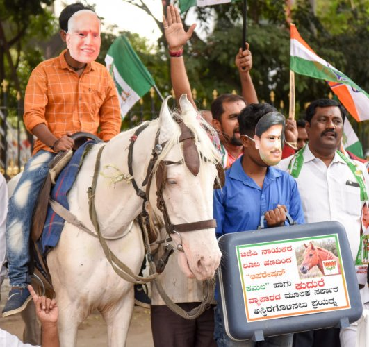 Congress members tage a protest accusing the BJP of horse-trading for capturing power in the state, in Bengaluru on Monday. DH Photo