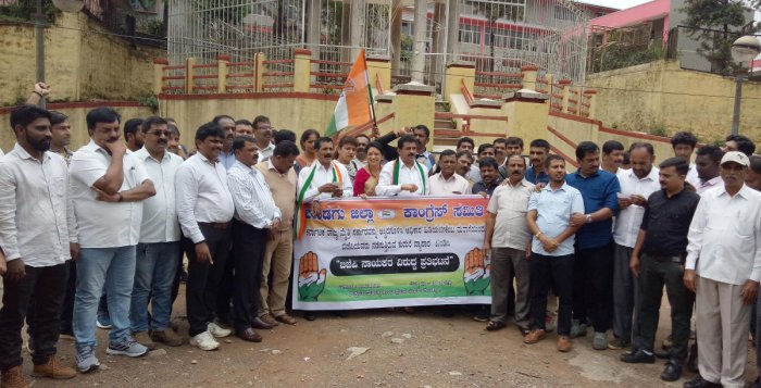 Congress leaders stage a protest against BJP in front of Gandhi Mantapa in Madikeri.