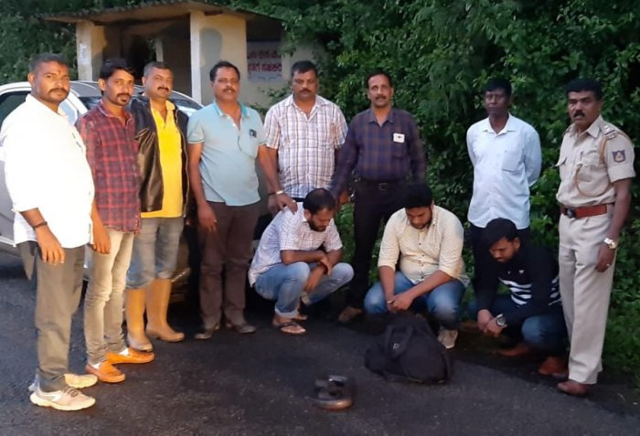 The accused (sitting) with the seized sand boa. The members of the Forest Department team (standing) which nabbed the accused are also seen.