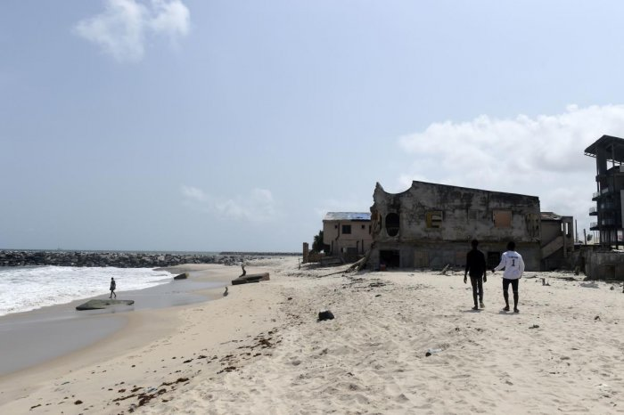 People walk along the beach toward houses destroyed by tidal erosion at Alpha Beach, a strip of the Lagos Coastline. (AFP Photo)