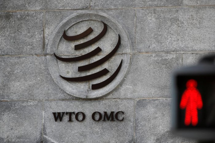 A logo is pictured outside the World Trade Organization (WTO) headquarters next to a red traffic light in Geneva, Switzerland. REUTERS