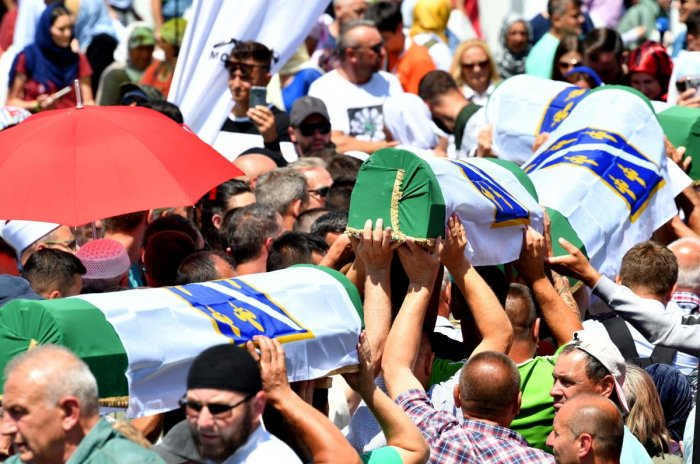 Bosnian Muslims carry caskets of the 33 newly identified bodies of the 1995 Srebrenica massacre before their inhumation at the Potocari memorial cemetery near the Eastern-Bosnian town of Srebrenica (AFP Photo)