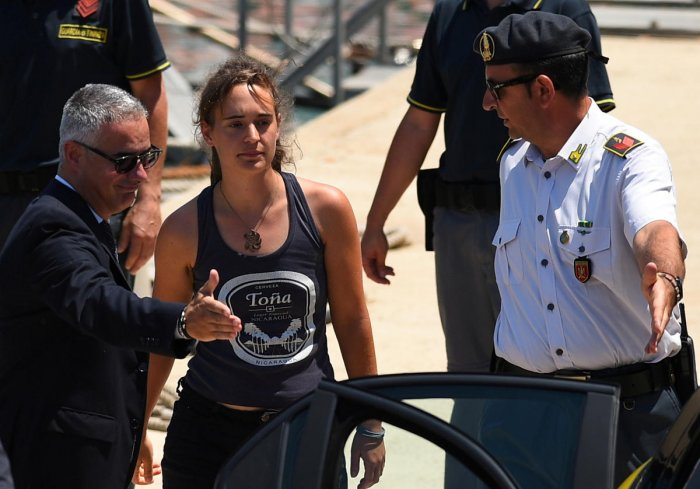 Carola Rackete, the 31-year-old Sea-Watch 3 captain, disembarks from a Finance police boat and is escorted to a car, in Porto Empedocle, Italy on July 1, 2019. (REUTERS File Photo)