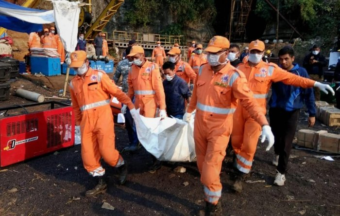 National Disaster Response Force (NDRF) and Indian Naval personnel carry an unidentified body of a trapped miner during a joint operation in Ksan area of East Jaintia Hills, Thursday, Jan. 24, 2019. (PTI Photo)
