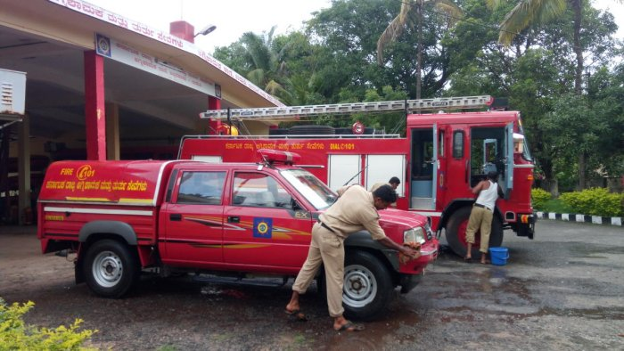 Firefighters involved in their routine work, including cleaning the vehicles and equipment checking, at District Fire Station in Udupi.