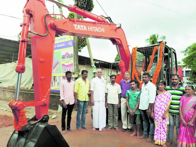 Ranjeeth, with his brother Pradeep, an endosulfan victim, and members of the family, is seen with the new excavator that was purchased with help from the Syndicate Bank's Venur branch in Andinje.
