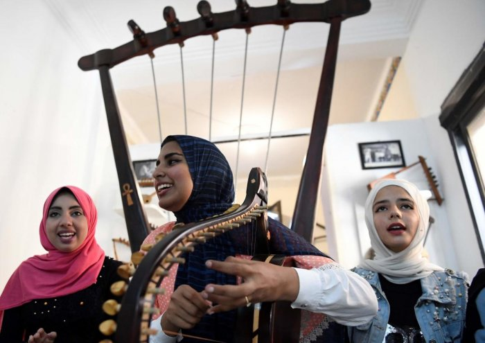 Iman Haddo plays a semsemia fan during a music session at the Canal 20 cultural museum in the northeastern city of Port Said. (AFP Photo)