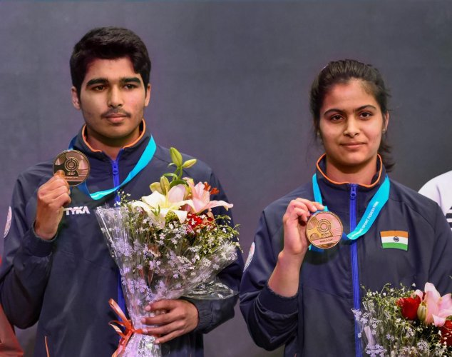 India's Saurabh Chaudhary and Manu Bhaker with their gold medals after winning the 10m air pistol mixed team event at the ISSF World Cup in New Delhi on Wednesday. PTI