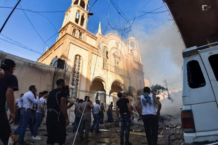 TOPSHOT - People gather at the scene of a car bomb explosion outside a church in the Kurdish-majority city of Qamishli in northeast Syria on July 11, 2019. - There was no immediate claim for the attack, which Syrian state television said left several peop