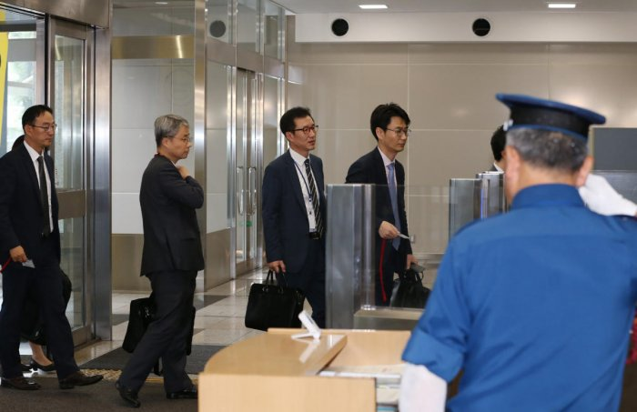 South Korea's officers enters the Ministry of Economy, Trade and Industry to hold a talk with their Japanese counterpart on the imposed restrictions, ending expedited shipments of chemical compounds used to manufacture microchips and smartphones in Tokyo
