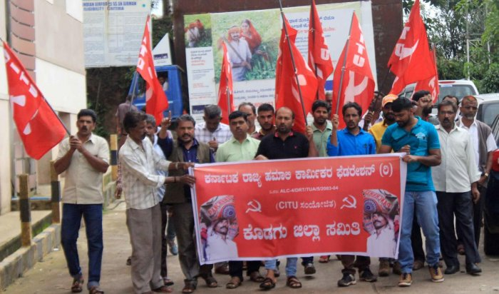 Members of Karnataka State Hamali Workers' Federation stage a protest in front of the deputy commissioner's office in Madikeri on Friday.