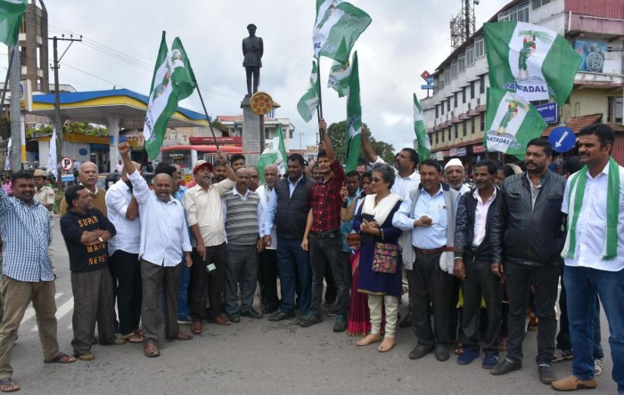 JD(S) workers stage a protest at General Thimayya Circle in Madikeri on Friday.