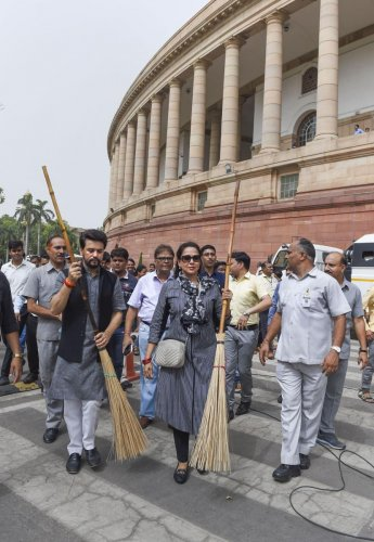 New Delhi: BJP MPs Anurag Thakur and Hema Malini participate in Swachhata Abhiyan at Parliament House, in New Delhi, on Saturday. PTI