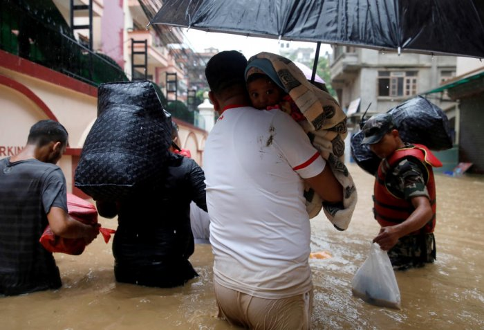 A man carrying a child walks towards the dry ground from a flooded colony in Kathmandu, Nepal July 12, 2019. REUTERS