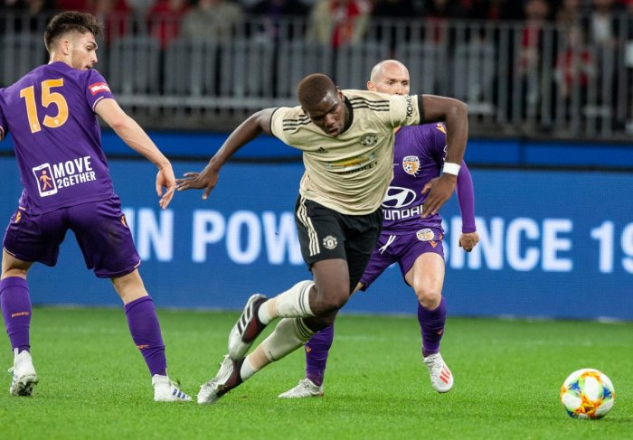 Manchester Paul Pogba (C) fights for the ball with Perth Glory's Chris Harold (L) and Gabriel Popovic (R) during their pre-season friendly match at Optus Stadium in Perth on July 13, 2019. TONY ASHBY / AFP